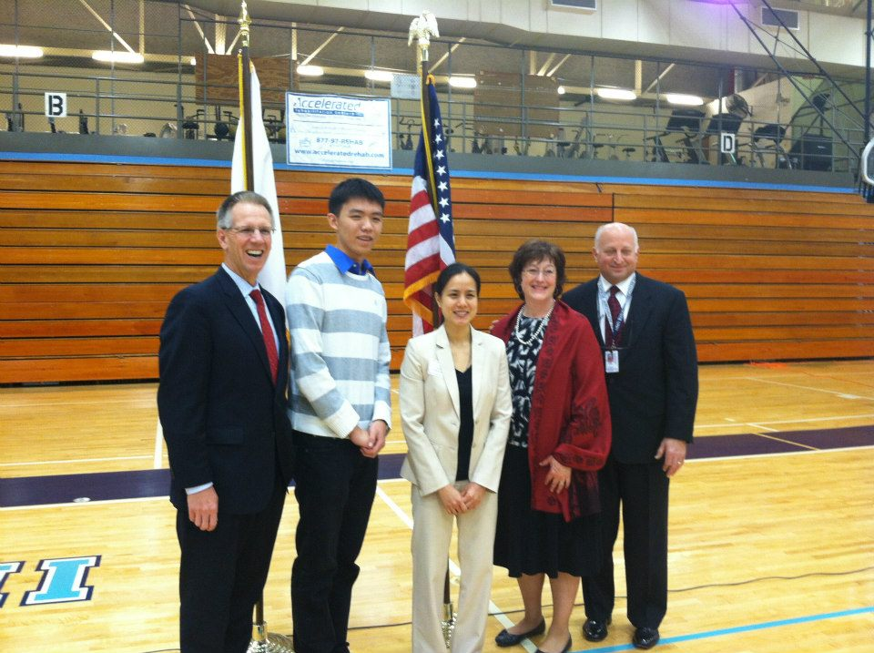Dr. Mas McGee, Kevin Zhang, Pearl Paovisaid, Dr. Diana Sharpe, and Jim Bondi gather for a photo after the assembly.