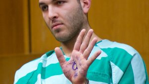 QAnon symbols on the hand of 24-year-old man in a courtroom charged for murder